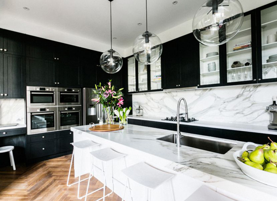 These black kitchen cabinets are the perfect complement to the marble walls and surfaces