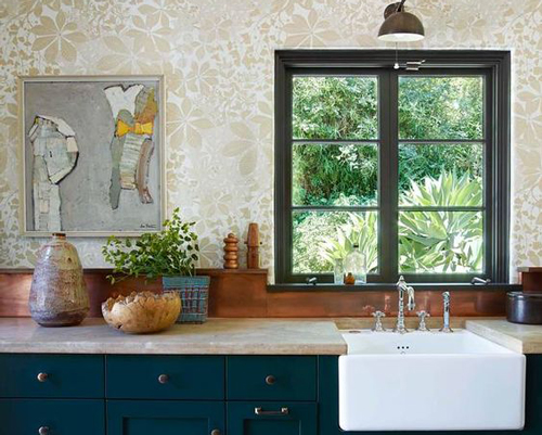 Here, the pale coloured wallpaper complements the dark upstands and cabinets.