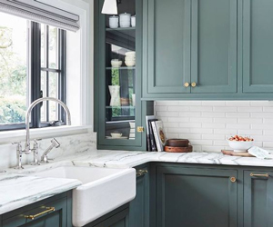 Marble worktops look great with these green kitchen cabinets.