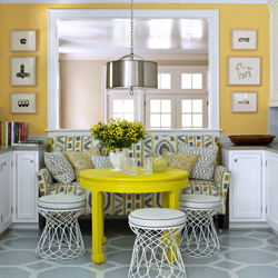This yellow breakfast nook utilises stools and a carefully placed sofa to create a welcoming space.