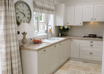 This pale stone kitchen flooring perfectly complements the neutral shade of the solid wood kitchen cabinets.