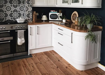 This kitchen matches the solid wood worktops with the kitchen flooring material.