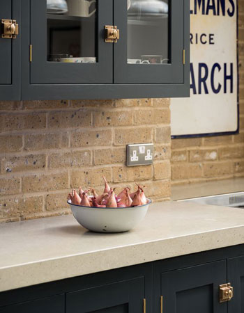 The exposed brickwork and solid concrete worktops give this kitchen an industrial style.
