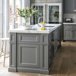 A grey kitchen with a slightly different shade of grey on the island and cabinets