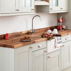 A grey kitchen with a walnut worktop