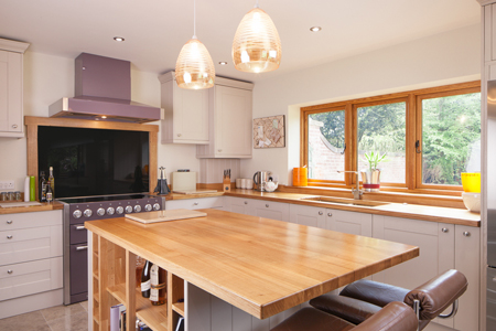 This solid oak kitchen features Shaker doors painted in Farrow & Ball's Elephants Breath.
