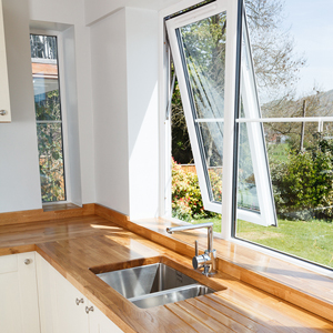 An airy neutral kitchen with large windows and an oak worktop