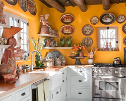 A Mexican kitchen style with bright yellow walls, decorative plates and light cabinetry