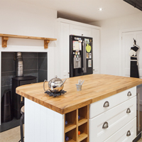 A monochrome kitchen with a double fridge-freezer, wood burning stove and an island featuring a wine fridge