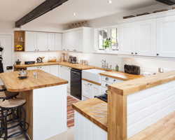 This classic kitchen combines oak worktops and cabinet doors in Farrow & Ball's All White for a fresh, traditional aesthetic.
