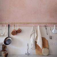 Dappled pink kitchen walls offer a striking effect, especially when set against white tiles.