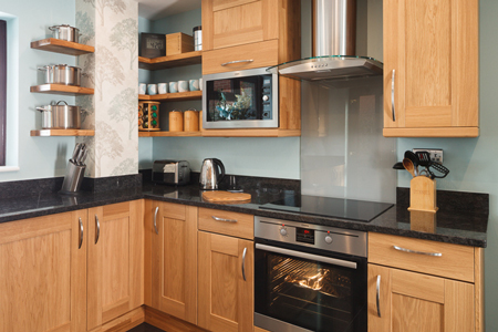 This kitchen has a black sparkle laminate worktop and unpainted Shaker doors.