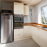 Stainless steel appliances in an open plan, neutral kitchen