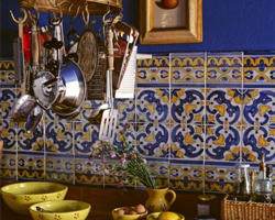 A Mexican kitchen style with deep blue walls, a tiled splashback and a hanging utensil rack
