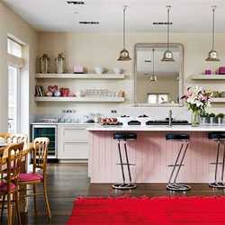 A traditional kitchen with a wooden island painted in Farrow & Ball's Calamine pink
