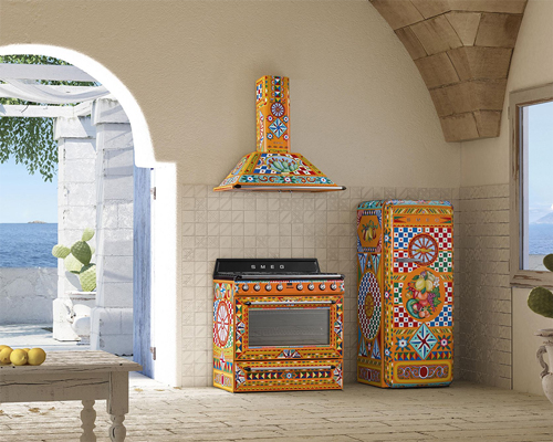 An open Mediterranean kitchen with an extremely vibrant Smeg fridge, oven and hood