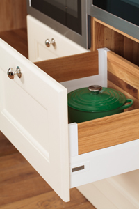 A wooden cabinet drawer with a polished handle and a green casserole dish