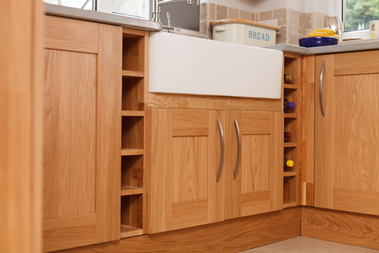 A wooden kitchen with a Belfast sink and wine racks