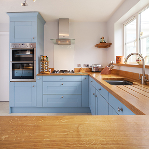A wooden kitchen with pale blue cabinets and stainless steel appliances