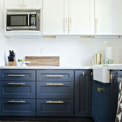 A kitchen with blue base cabinets, white wall cabinets and gold handles