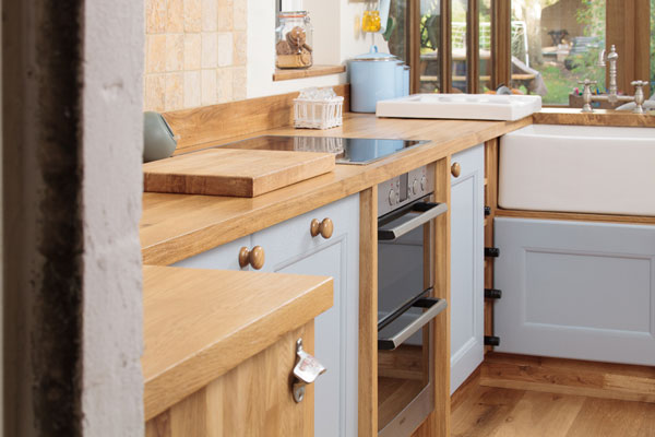 A kitchen with wooden worktop, blue cabinets and a stainless steel oven