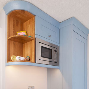 Blue cabinets and a open-ended oak shelf with colourful hand-painted accessories.