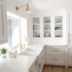 A bright white kitchen with marble worktop and gold handles, taps and lights