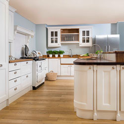 A bright kitchen with white cabinets and mis-matched worktops