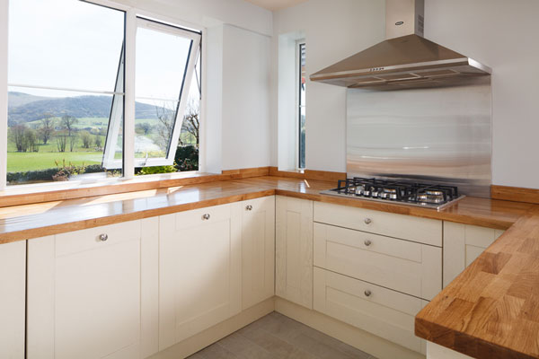 A large bright kitchen with a wooden worktop and open window