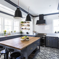 A patterned floor makes a statement in this kitchen with dark blue cabinetry and bright white walls.