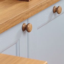 Traditional-style cabinets painted in a light blue and topped with a solid oak worktop.