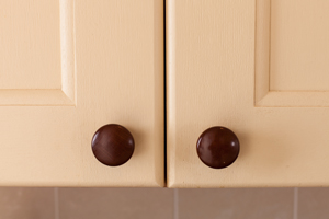 Cream painted oak cabinet doors with wooden knobs.