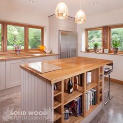 An oak kitchen island with oak end panels painted in Elephant's Breath solid oak kitchen cabinets.