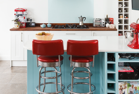 The combination of Farrow & Ball's Blue Ground with red accessories creates a wonderfully retro feel in this wooden kitchen.