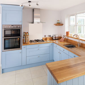 A light kitchen with cabinets in Farrow & Ball's Lulworth Blue, stainless steel appliances and full-stave oak worktops.