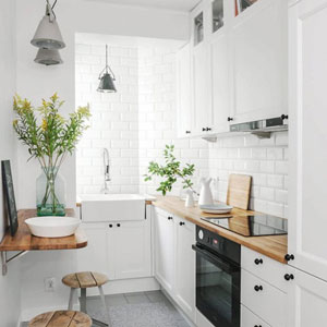 The sink positioned at the end of the kitchen and maximised use of vertical space allow room for a small seating area in this galley kitchen design