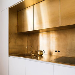 This white kitchen features a striking gold backsplash, worktop and accessories