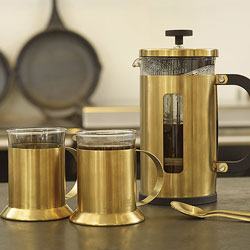 A gold cafetiere with gold mugs and teaspoons on a kitchen worktop