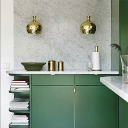 A green kitchen with gold toned lights and accessories