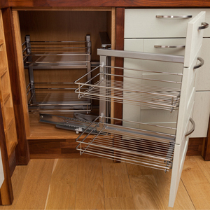 Handy wirework storage solutions help to keep solid wood kitchens uncluttered.