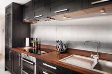 Black painted kitchen with stainless steel sink and steel splashback.