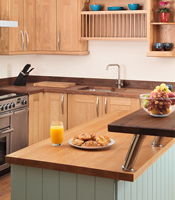 Kitchen island with oak cabinets, full stave Prime Oak worktop and breakfast bar.