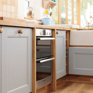 A kitchen with oak worktops, pale blue cabinets, a Belfast sink and a modern oven