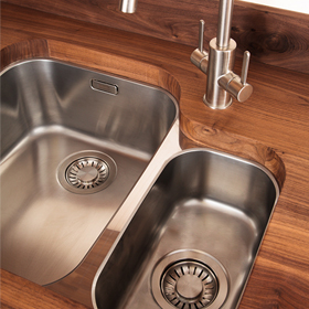 An undermounted 1.5 bowl stainless steel kitchen sink with left-hand main bowl.