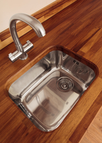A large undermounted single bowl stainless steel kitchen sink.