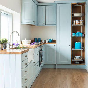 This kitchen uses a tall cabinet to make the most of the available space and light available