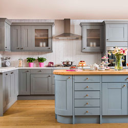 A kitchen featuring a blue island and grey cabinets