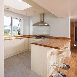 A neutral kitchen with breakfast bar, skylight and a countryside view