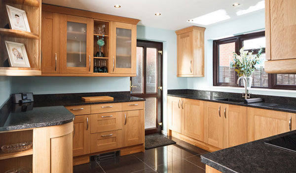 A kitchen with oak cabinets, black worktops, pale blue walls and spotlights