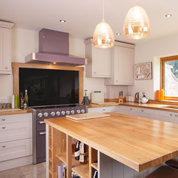 A kitchen with wooden island, purple oven and extractor fan, and gold pendant lamps